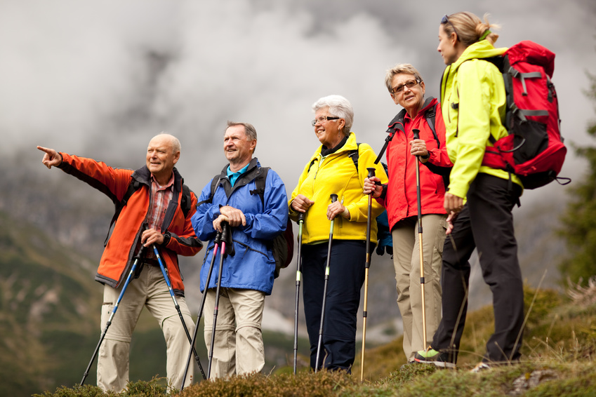 groupe d'amis seniors en randonnée sur fond de ciel nuageux